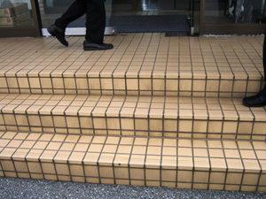 雨の日に転倒する社屋入口の磁器タイルの階段